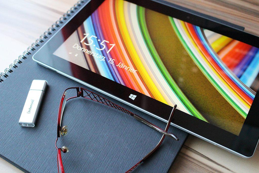 USB Stick, Tablet und Brille auf Schreibtisch